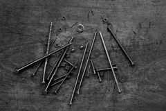 Set of golden screws, bolts, nails, washers, nuts on wooden back Royalty Free Stock Image