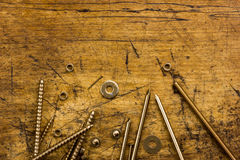 Set of golden screws, bolts, nails, washers, nuts on wooden back Stock Images