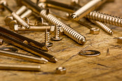 Set of golden screws, bolts, nails, washers, nuts on wooden back Stock Photos