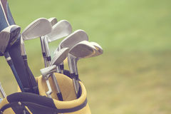 Set of golf clubs over green field royalty free stock photo