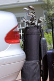 Set of golf clubs beside parked car on driveway, close-up stock image