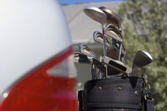 Set of golf clubs beside parked car on driveway, close-up (differential focus) Stock Photography