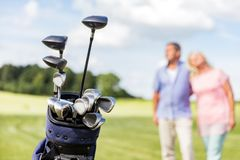 Set of golf clubs with senior couple in the background. stock image