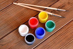 Set of gouache paints and two brushes on a brown wooden background Royalty Free Stock Image
