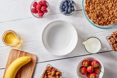 A set of granola ingredients, banana, honey, milk, berries and an empty plate for a healthy breakfast. Step-by-step Royalty Free Stock Photos
