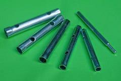 Set of gray metal tubular end keys on a green table. Set of gray metal tubular end keys on a green background Royalty Free Stock Image