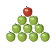 Symbol of hierarchy. Set of 9 green apples of the same shape and size set in a pyramid shape with a chief red apple on the top Stock Image