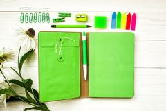 Set of green fashion and stylish stationary top view. Bright green notebook and other creative stationary on white wooden background Royalty Free Stock Image
