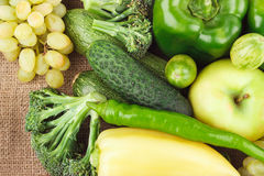 Set of green fresh raw vegetables and fruits on the burlap Royalty Free Stock Photo