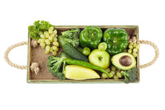 Set of green raw vegetables and fruits in the wooden tray, isolated Royalty Free Stock Photos