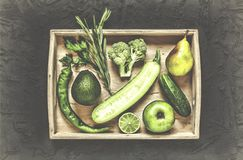 A set of green vegetables and fruits in a wooden box. On a black stone photo. The concept: healthy food, cancer prevention and heart disease. Top view Royalty Free Stock Photos