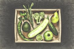 A set of green vegetables and fruits in a wooden box. On a black stone photo. The concept: healthy food, cancer prevention and heart disease. Top view Stock Images
