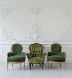 Set of green wooden vintage chairs standing in front a white wall design bas-relief stucco mouldings roccoco elements on light par Stock Image