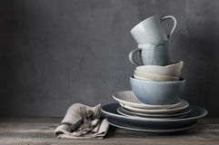 Set of grey crockery. Stack of grey crockery and silverware on rustic wooden table against shabby gray wall. Various plates, dish, bowls and mugs stock image