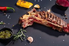 Set of grilled sliced T-bone steak with grilled corn, sauce, chilli, rosemary, salt, garlic on black background stock photos