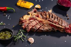 Set of grilled sliced T-bone steak with grilled corn, sauce, chilli, rosemary, salt, garlic on black background stock image