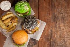 Set gruli z kumberlandem i warzywa na starym drewnianym tle trzy mini domowej roboty hamburgeru, Idaho, pojęcie szybkie żarcie a fotografia stock