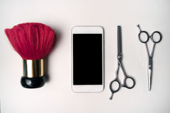 Set of hairdressing scissors, smart phone and neck brush Royalty Free Stock Photos
