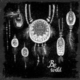 Set of hand drawn ethnic jewelry pendants, feathers and text on black background. Be wild Royalty Free Stock Photo