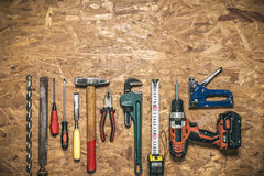 A set of hand tools in a row on the panel of OSB Royalty Free Stock Photos