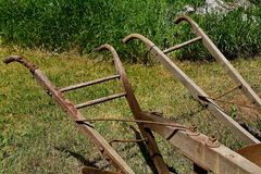 Handles of an antique horse drawn plow. Set of handles for plowman to hold behind a one bottom horse drawn plow royalty free stock image