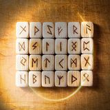Set of Handmade scandinavian wooden runes on a wooden vintage background in a circle of light. Concept of fortune stock images