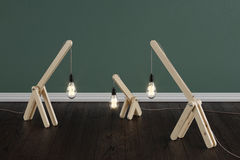 A set of handmade wooden lamps in the room on a dark brown floor with dark green walls. Stock Images