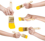 Set of hands with flat paint brush with yellow tip Stock Images
