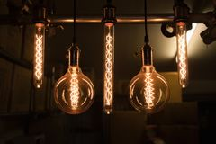Set of hanging light bulbs with dark storage room background. Retro style. Close up group of hanging light bulbs with storage room background in darkness. Retro Stock Image