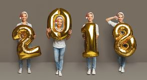 Collage of girl with 2018 number balloons portraits. Set of happy young woman with 2018 gold number balloons portraits. Smiling girl in santa hat positive Stock Image