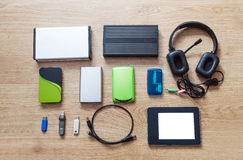 Set of hard drives, memory cards, card reader, tablet, phones. Lying on wooden floor closeup Royalty Free Stock Photos