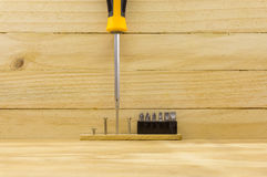 Set head screw driver and screw. On wood background Royalty Free Stock Images