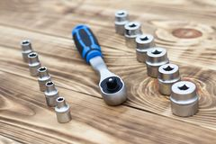 set of heads for car repairs. ratchet on a wooden blue background. ratchet close-up stock photos