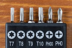 Set of heads for screwdriver bits on a wooden table royalty free stock photo