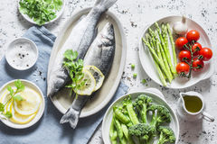 Set of healthy balanced ingredients for lunch - sea bass, asparagus, tomatoes, broccoli, green peas, olive oil and spices. On a li Stock Images