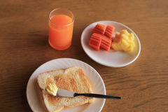 Set of healthy breakfast, plate of toast with butter and fresh fruits and orange juice. Set of healthy breakfast, plate of toast with butter and fresh fruit and Stock Photography