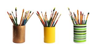 Set of holders with different paint brushes stock photography