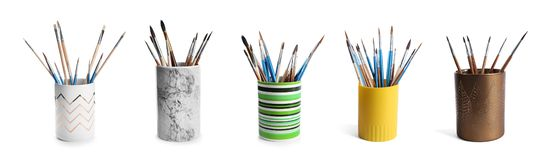 Set of holders with different paint brushes. On white background stock image