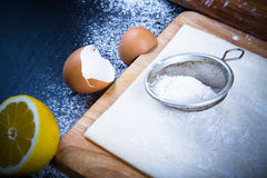 Set for home baking on a black background with flour. Dough, boa Royalty Free Stock Images