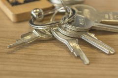 Set of home keys detailed. Set of detailed metallic home keys on the wood table royalty free stock images