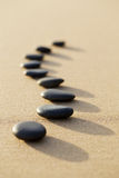 set of hot stone on white sand calm beach in backbone shape. selective focus, spa concept stock photography