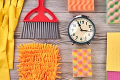 Set of house cleaning items, top view. Gloves, sponges, rags, brushes for cleaning and alarm clock on laminate floor. Time for cleaning stock images