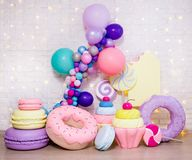 Set of huge artificial sweets and pastry decorations over white brick wall royalty free stock photos