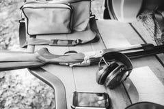 Set hunter shotgun headphones smartphone bag compartment jeep. Set of hunter shotgun headphones smartphone bag on the luggage compartment cover of the jeep Stock Image