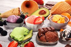 Set of ice cream scoops of different colors and flavours with berries, chocolate and fruits. On table royalty free stock photography
