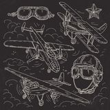 Set icons retro old aircraft, pilot helmet and glasses pilot drawn on black background. Vector illustration, set icons retro old aircraft on a background of Royalty Free Stock Images