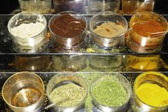 Set of Indian spices on bowls, green, red, yellow, white, brown with spoons royalty free stock photo