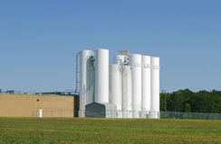 Set Of Industrial Storage Silos. A set of industrial silos attached to a light industrial food processing facility Stock Photos