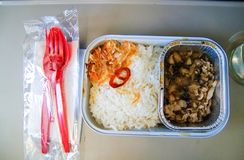 Set of inflight meal in a box, on the folding table in economy class. Feeding the passengers of Asian food on the plane . royalty free stock photo