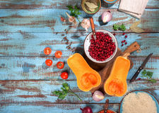 Set of ingredients for cooking healthy vegetarian food. Pumpkin, cranberries, onions, garlic, rice, parsley, oil and tomatoes on a wooden table with copy space Royalty Free Stock Images